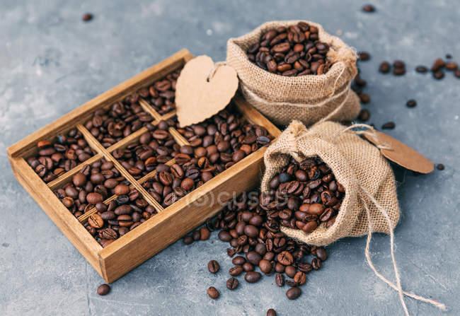 Primer plano de molinillo de café y caja de granos de café - foto de stock
