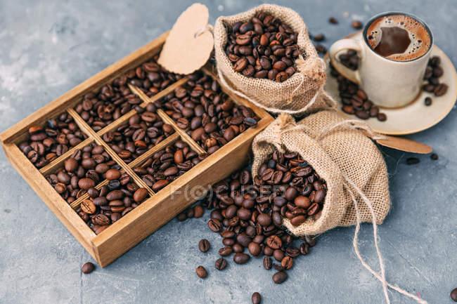 Деревянная коробка и мешки с кофейными зёрнами — стоковое фото