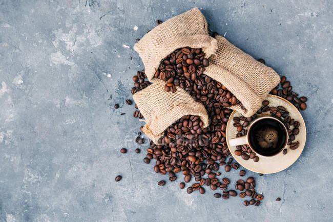 Sacks with coffee beans and cup of coffee — Stock Photo