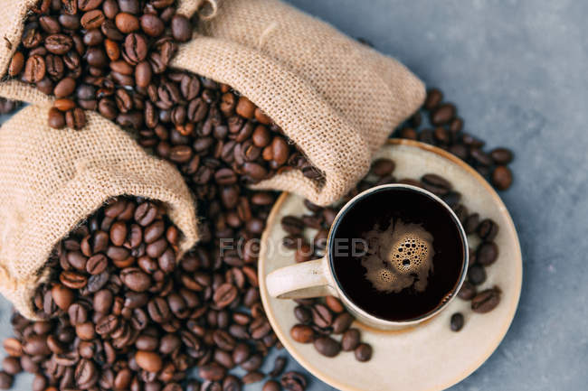 Coffee cup and coffee beans over table — Stock Photo