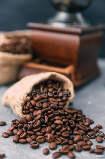Großaufnahme von Kaffeemühle und Säcken mit Kaffeebohnen — Stockfoto