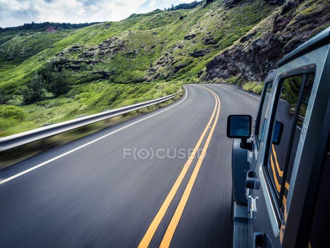 Coche que viaja a lo largo de la carretera sinuosa, Maui, Hawaii, América, EE.UU. - foto de stock