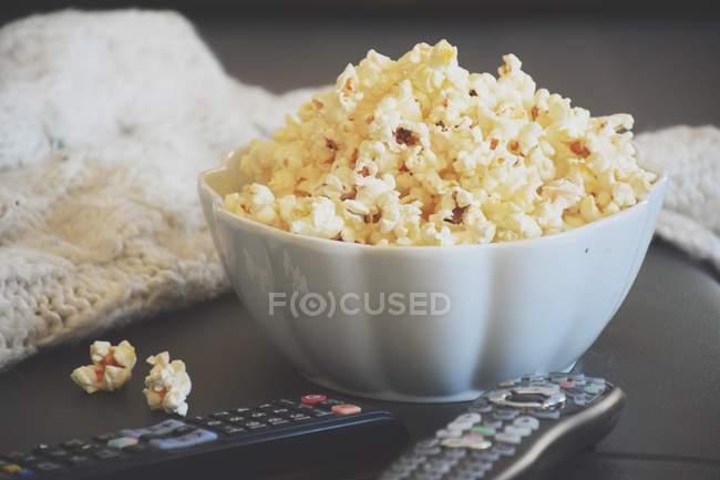 Un bol de pop-corn avec les télécommandes Tv — Photo de stock