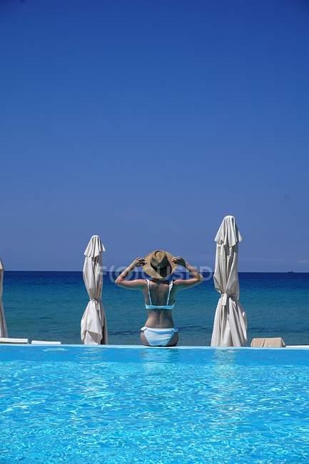 Mulher em biquíni sentada à beira de uma piscina junto ao mar — Fotografia de Stock