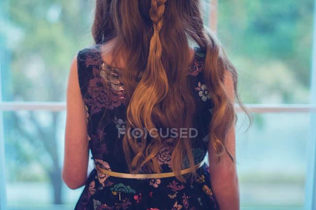 Visão traseira de uma menina em um vestido de festa olhando para fora de uma janela — Fotografia de Stock