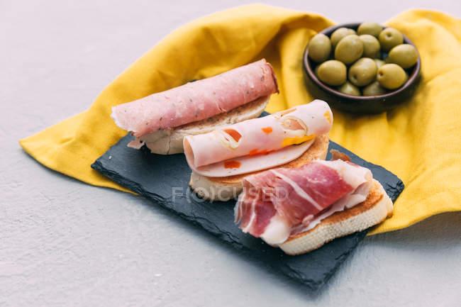 Bruschetta aux charcuteries et un bol d'olives — Photo de stock