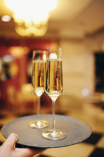 Man carrying a tray with two glasses of champagne — Stock Photo