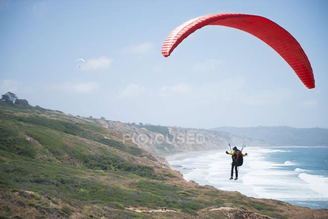 Человек на параплане над береговой линией, Ла-Хойя, Калифорния, Америка, США — стоковое фото