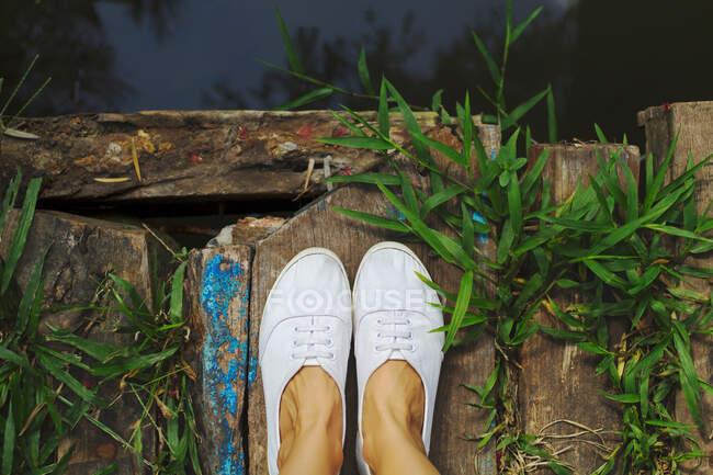 Close-up de pés de uma mulher em pé em uma ponte de madeira — Fotografia de Stock