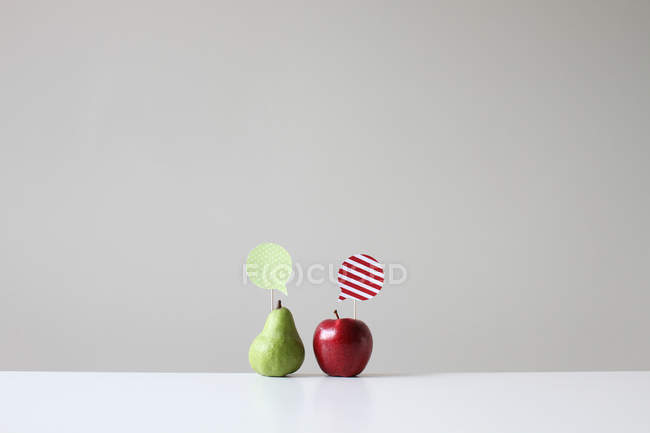 Conceptual apple and pear with speech bubbles — Stock Photo
