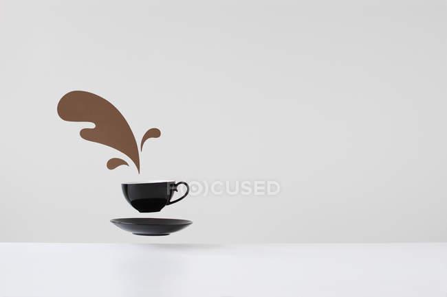 Café derramado conceptual de taza flotante y platillo - foto de stock