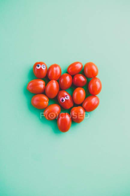 Tomates da ameixa com olhos googly em uma forma do coração — Fotografia de Stock