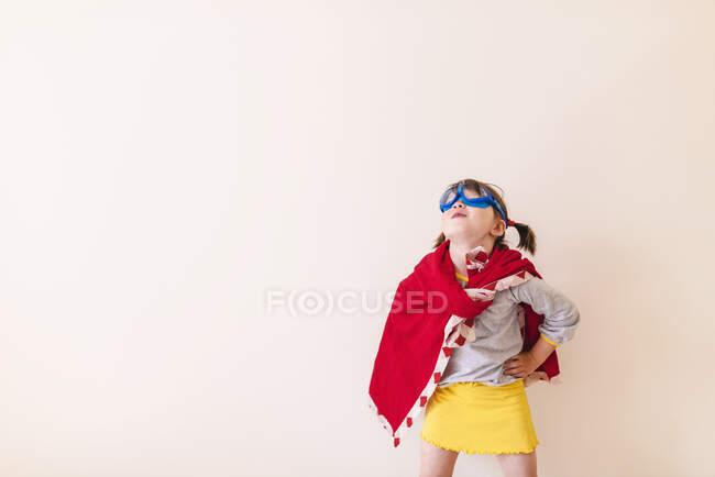 Девушка, одетая как супергерой на белом фоне — стоковое фото