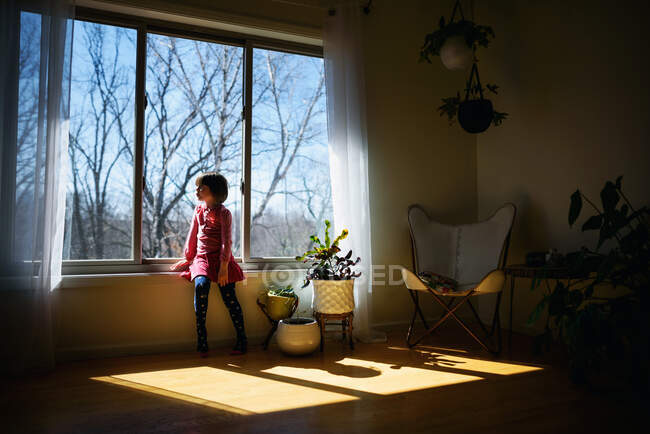 Девушка, сидящая на солнце и смотрящая в окно — стоковое фото