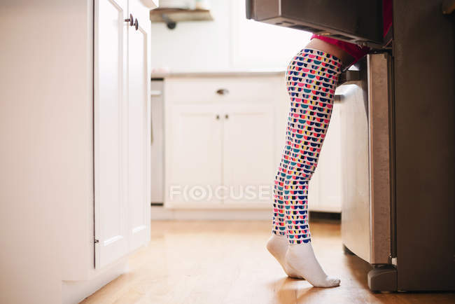 Girl standing by an open refrigerator, side view — стокове фото