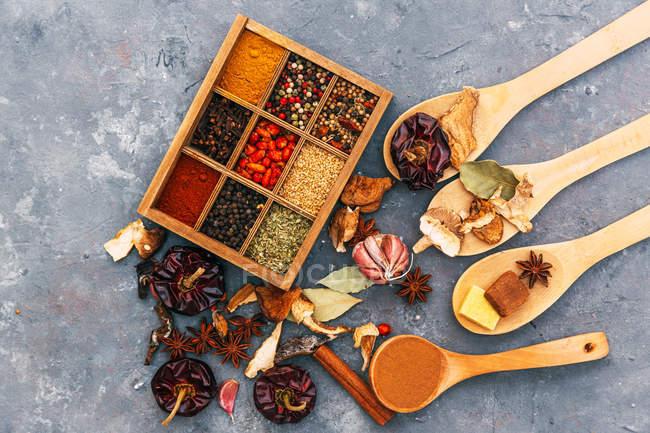 Hierbas y Especias en una caja de madera con cucharas - foto de stock