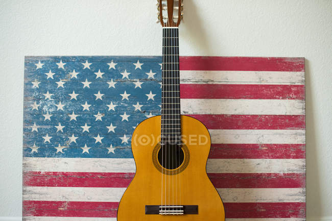 Guitarra inclinada contra una bandera americana pintada en madera - foto de stock