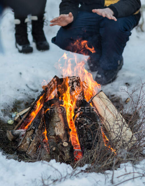Man crouching by a campfire in the snow warming his hands — Stock Photo