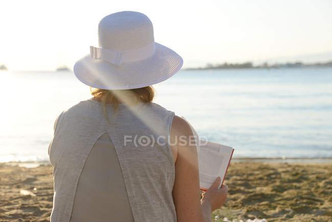 Donna seduta sulla spiaggia a leggere un libro — Foto stock