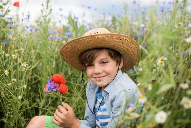 Lächelnder Junge, der in einem Feld von Wildblumen sitzt und einen Blumenstrauß hält — Stockfoto