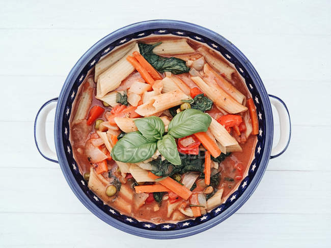 Bowl of vegetarian pasta with peppers, carrots and basil — Stockfoto