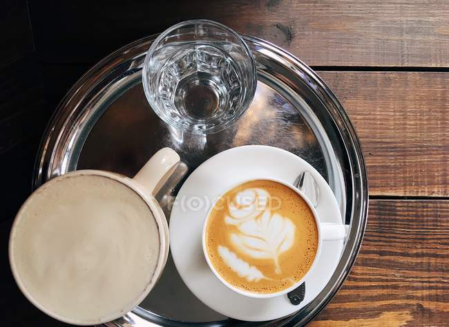 Top view of Flat white coffee, cappuccino and glass of water on a tray — Stock Photo