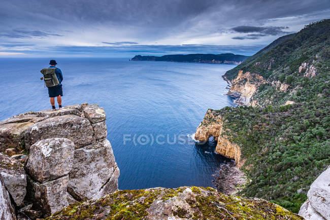 Homem olhando por cima litoral de três capas de pista, Mount Fortescue, Tasmânia, Austrália — Fotografia de Stock