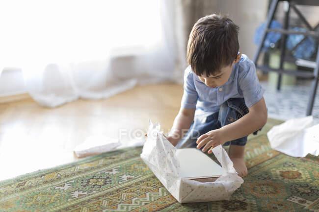 Мальчик, сидящий на полу и разворачивающий подарок на день рождения — стоковое фото