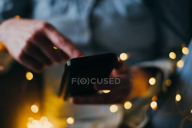 Mujer usando su teléfono inteligente cerca de las luces de hadas - foto de stock
