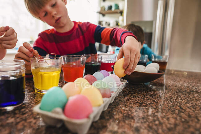 Dos chicos de pie en la cocina muriendo huevos de Pascua - foto de stock