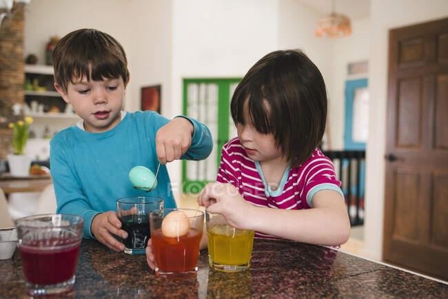 Niño y niña de pie en la cocina muriendo huevos de Pascua - foto de stock