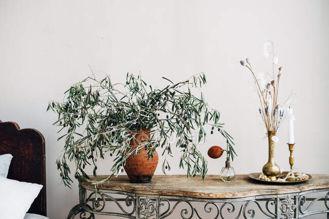 Branches in a vase with a candle on a sideboard table — Stock Photo