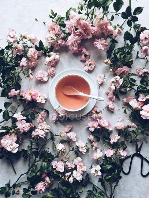 Cup of herbal tea with dried roses — Stock Photo