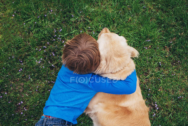 Overhead view of a boy hugging his golden retriever dog — Stock Photo