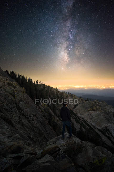 Man standing on Baldy Mountain looking at stars with Fresno in the distance, California, America, USA — Stock Photo