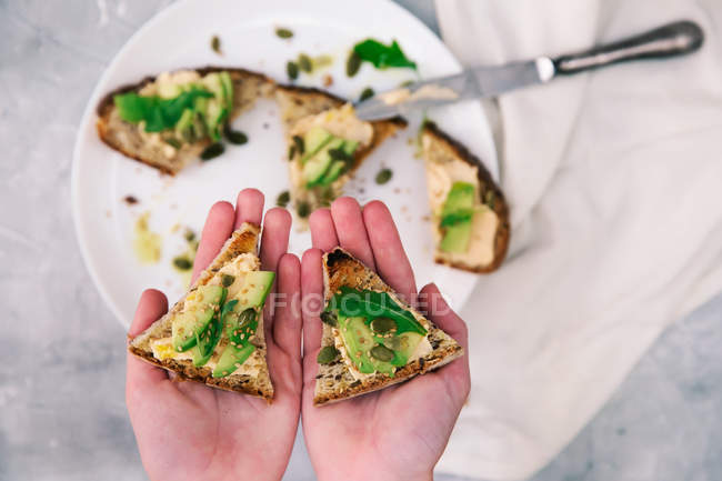 Woman hands holding avocado and brie toast — стокове фото