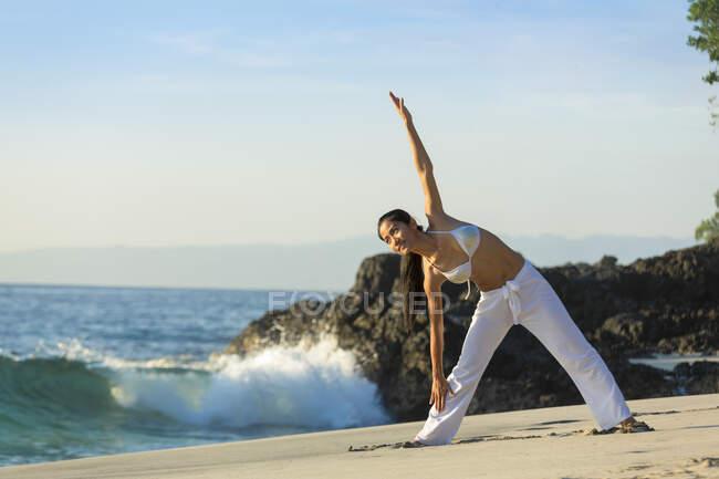 Молодая азиатка занимается йогой на белом песчаном пляже на Бали. На ней длинные белые брюки и бикини. — стоковое фото
