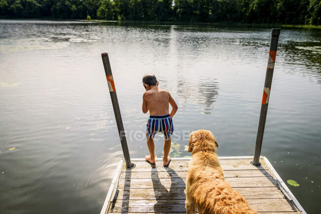 Young boy thinking about leaping off a dock into a lake with a dog — стокове фото