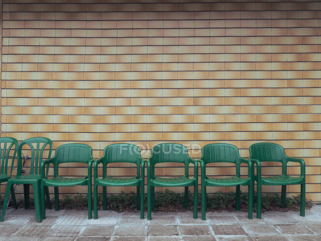 Row of chairs against a brick wall — Stock Photo