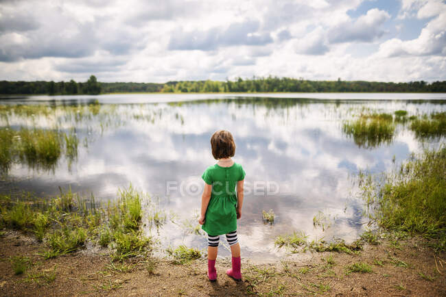 Young girl looking at peaceful lake with reflection of sky and clouds — Stock Photo