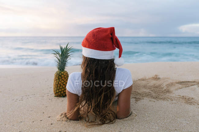 Woman wearing a Christmas Santa hat lying on beach next to a pineapple, Haleiwa, Hawaii, America, USA — Stock Photo
