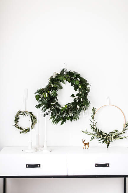 Wreaths hanging on a wall by a sideboard — Stock Photo
