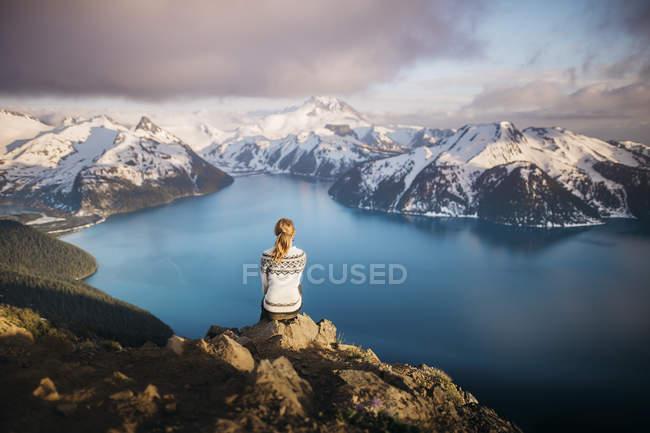 Woman sitting on rocks looking at view, Lake Garibaldi, British Columbia, Canada — Stock Photo