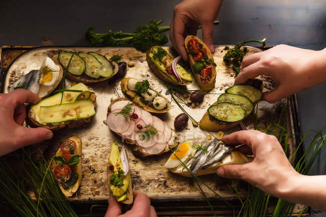 Four people eating open sandwiches — Photo de stock