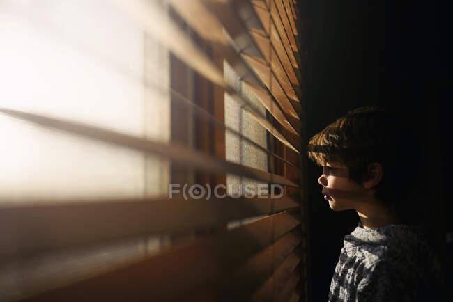 Niño de pie junto a una ventana mirando a través de las persianas - foto de stock