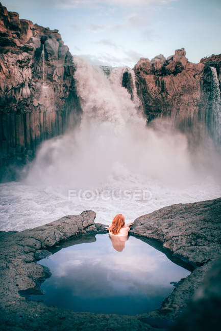Rear view of a woman in a rock pool looking at Aldeyjarfoss waterfall, Highlands, Iceland — стокове фото