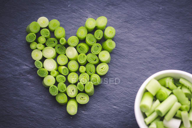 Fatias de alho-porro em uma forma do coração, vista superior — Fotografia de Stock