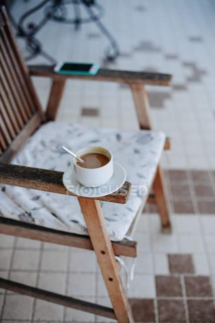 Teléfono móvil y una Copa de chocolate caliente en el brazo de una silla - foto de stock