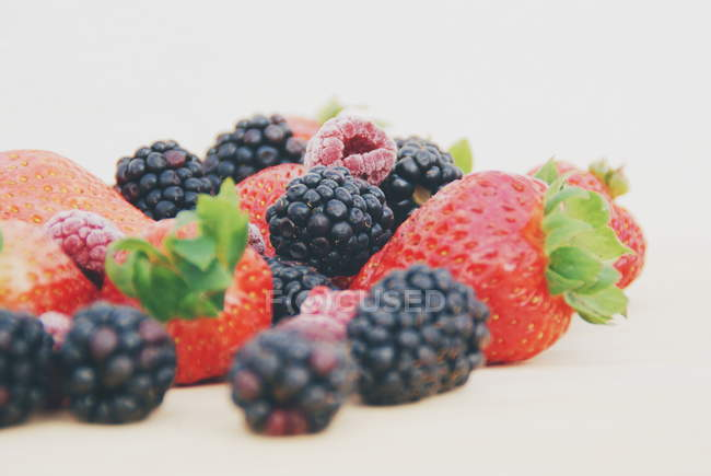 Strawberries, blackberries and raspberries on a chopping board — Stock Photo