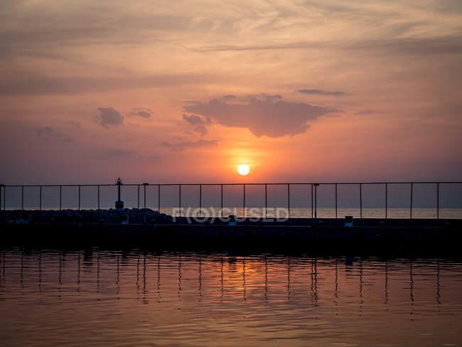 Mur du port en mer et balustrades au coucher du soleil — Photo de stock